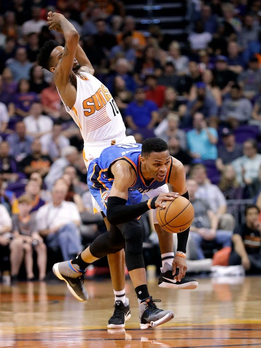 Phoenix Suns forward Derrick Jones Jr. (10) avoids a foul with Oklahoma City Thunder guard Russell Westbrook during the first half of an NBA basketball game, Friday, April 7, 2017, in Phoenix. (AP Photo/Matt York)