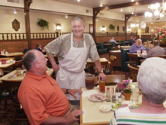 """Clad in an apron, Heritage Cafeteria owner Mike Lohmeyer chats with customers Bill Smillie, left, and his mother, Dahlia Smillie, at the Sunshine Street location of the eatery. It closed not long after this photo was taken in 2002, leaving only the Battlefield Road cafeteria, which itself closed in 2016. For several years before the Sunshine Street store shuttered, it was rebranded """"Mrs. O'Mealey's."""""""