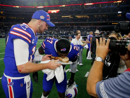 Buffalo Bills quarterback Josh Allen holds a plate with a turkey leg as cornerback Tre'Davious White (27) leans over to take a bite as they participate in a post game broadcast interview following their NFL football game against the Dallas Cowboys in Arlington, Texas, Thursday, Nov. 28, 2019. (AP Photo/Michael Ainsworth)