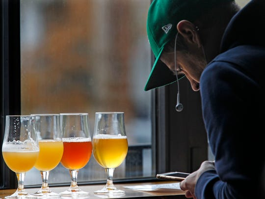 A.J. Zydzik, of Milwaukee, samples a, Opalescence (a double IPA; Plumpy (a smoothie beer; and the Florisconsin, a Saison, during a visit to 1840 Brewing Co.