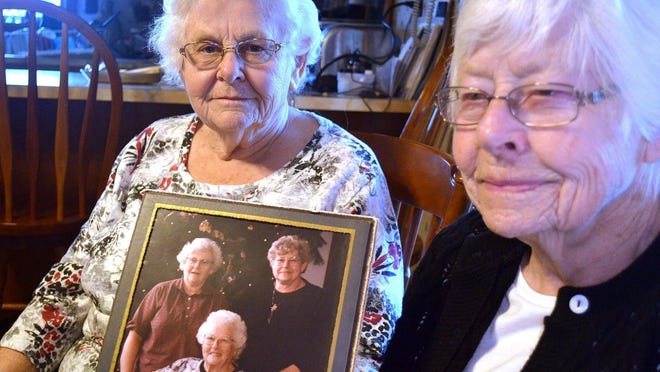 Sisters Susie Armstrong, 83, and Shirley Clark, 88, at Armstrong's home in Stoneboro, Mercer County, Pa., hold a photo of themselves with their mother, Grace Vath, seated. The sisters have been searching for their older brother, who may have been born at the Veil Maternity Hospital in Corry, Pa., in about 1926.