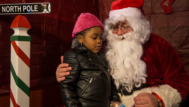 Ta'syia Foster, 5, of Asbury Park, with Santa. The Asbury Park Toy Drive helps hundreds of needy families receive toys for their children as well as coats, hats, scarves, and gloves for the winter.