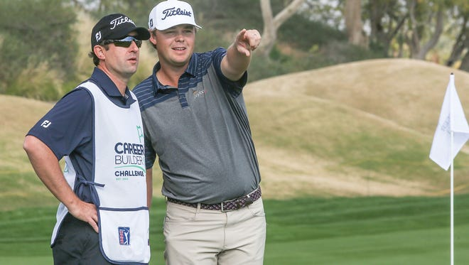 Patton Kizzire and caddie look around the course on the green of the 9th hole at the Jack Nicklaus Tournament Course at PGA West during the Careerbuilder Challenge, January 19, 2016.