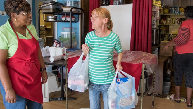 Barbara Hilderbrand, right, chats with Pastor Sylvia Tisdale after getting some food at the Epps Christian Center food pantry in Pensacola on Thursday, January 19, 2017.  This food pantry is one of the resources that is referred by the United Way's 2-1-1 service.