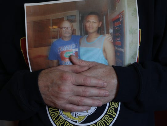 Tom Swann, a disabled veteran, holds a photo of him