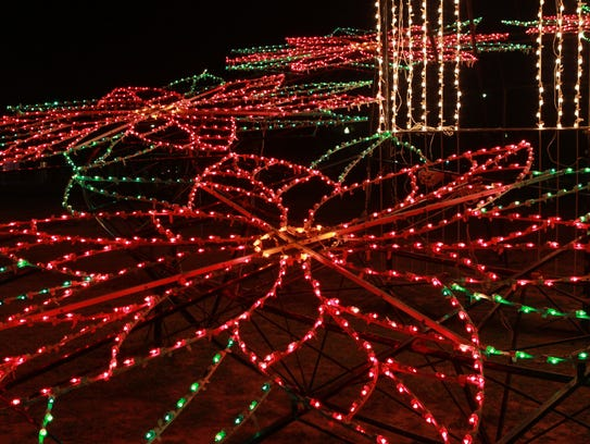 Lighted flowers shine along the banks of the Concho
