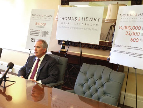 Attorney Thomas J. Henry speaks at a press conference