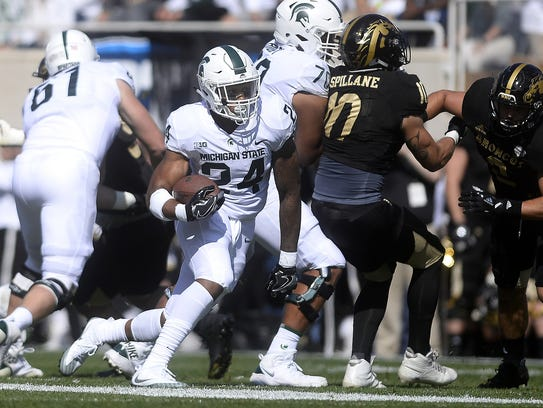 Michigan State's Gerald Holmes runs for a gain during