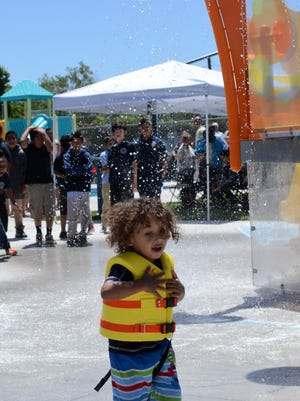 Atlas Grey Calvin, 4, flees water falling from Traner Pool's new waterpark-style jungle gym during the grand reopening of the community pool on June 11, 2018.