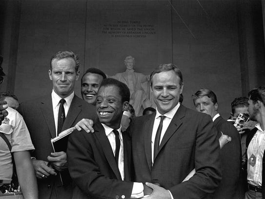 Marlon Brando poses with his arm around James Baldwin,