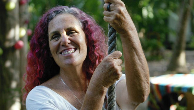 In this file photo, Shawnee Chasser smiles as she hangs onto a rope swing next to her treehouse in 2007 in Miami.