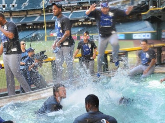 Dodgers players jump into the pool at Chase Field after clinching the NL West title.