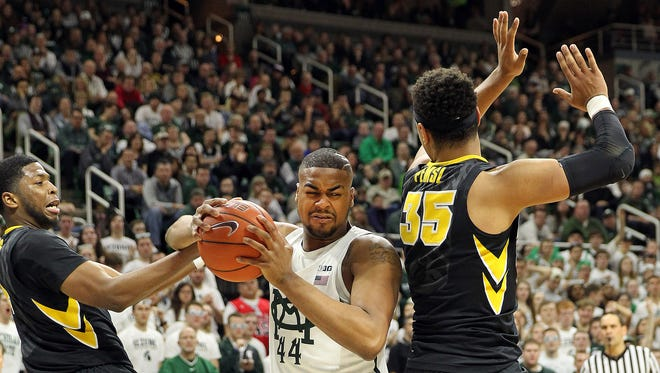 Feb 11, 2017; East Lansing, MI, USA; Michigan State Spartans forward Nick Ward is defended by Iowa Hawkeyes forward Tyler Cook and forward Cordell Pemsl during the second half at the Jack Breslin Student Events Center.