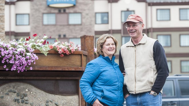 Contractor Brad Talcott and his business partner and wife, Linda Caricaburu, stand outside their projects, StayBridge Suites and The Front Brewing Company. They and other partners now are building the West Bank Landing project.