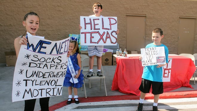 From left to right: Isabella Haas, 10, Valentina Martinez, 5, Sebastian Martinez, 11, and Jody Cerra, 7, stand outside of Wal-Mart Thursday and collect donations for those affected by Hurricane Harvey.