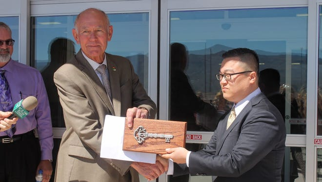 Alamogordo Mayor Richard Boss presents the key to the family fun center to Downtown Venture Corp. CEO  Jay Chun during a ceremonial key exchange Monday.