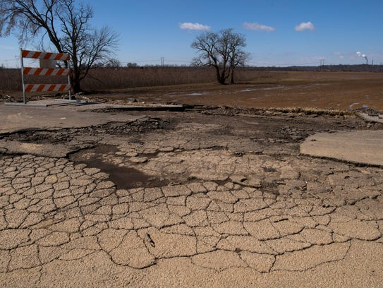 The top layer of asphalt washed-out into the farm field