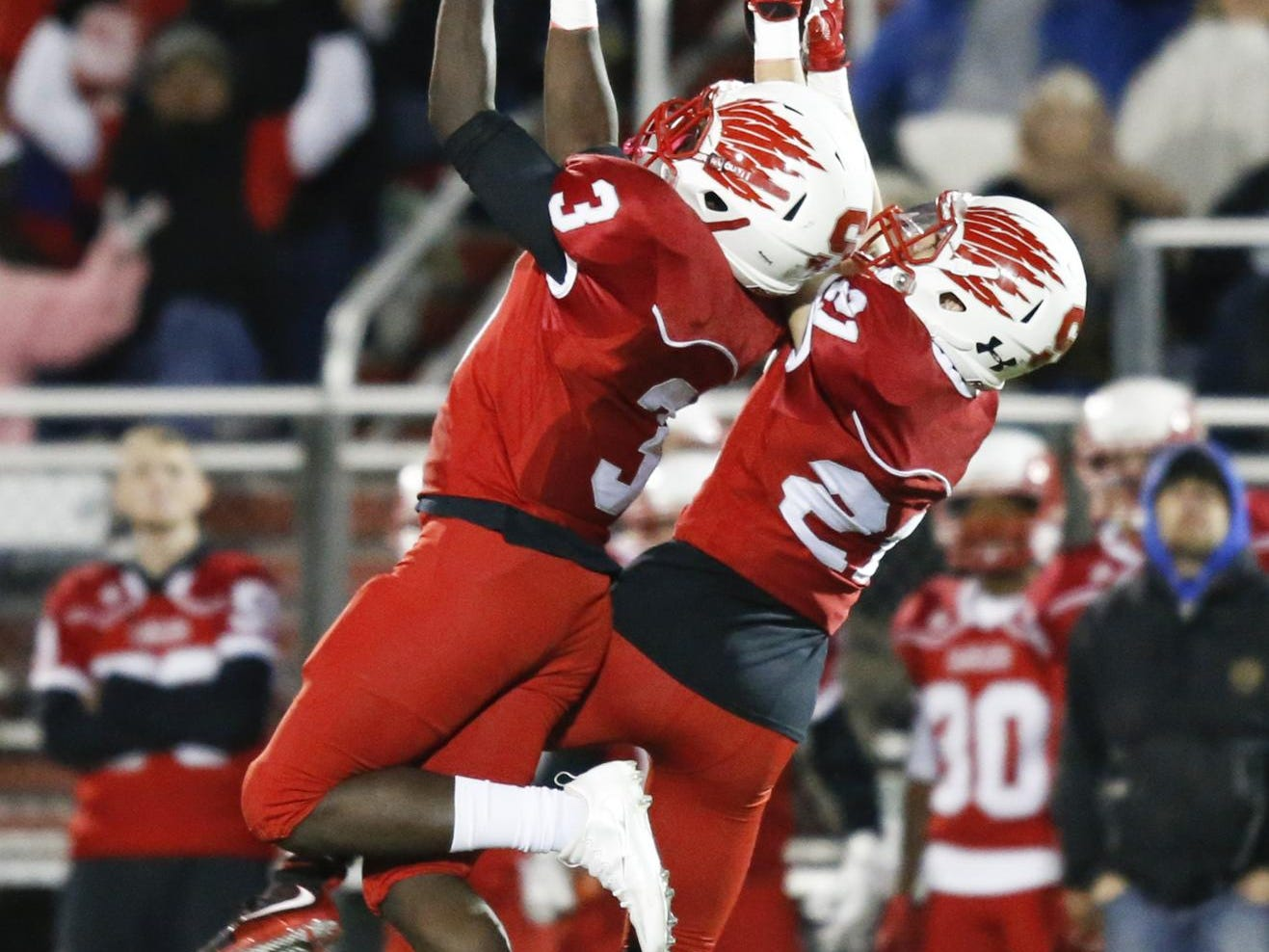 Smyrna defensive backs Larsen Wilson (3) and Jacob Soroko vie for an interception, taken in by Wilson, in the second quarter of a DIAA Division I state tournament semifinal Friday at Smyrna High School.