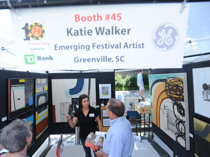Katie Walker, an Artisphere emerging artist, speaks with festival goers at her booth on Sunday, May 11, 2014.