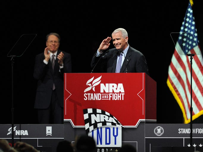 Lt. Col. Oliver North, USMC (Ret.) speaks at the NRA Stand and Fight Rally as Wayne LaPierre, executive vice president of the NRA, looks on during the 143rd National Rifle Association Annual Meeting at Lucas Oil Stadium, Saturday, April 26, 2014, in Indianapolis.