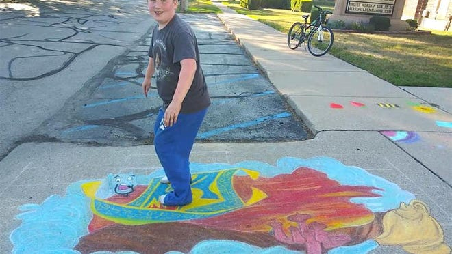"""Jonathon Comiskey, 9, of Blissfield shows off an art creation representing the story of Aladdin and the magic lamp, which was created by his mother, Elizabeth, for this year's virtual Art at Your Feet event in Blissfield. Now named """"Art on the Feed,"""" due to the transition to the digital world because of the coronavirus pandemic, individuals in the Blissfield community and beyond are encouraged to craft some street chalk art creations and post photos of the art to social media for judging and the possibility of winning cash prizes."""