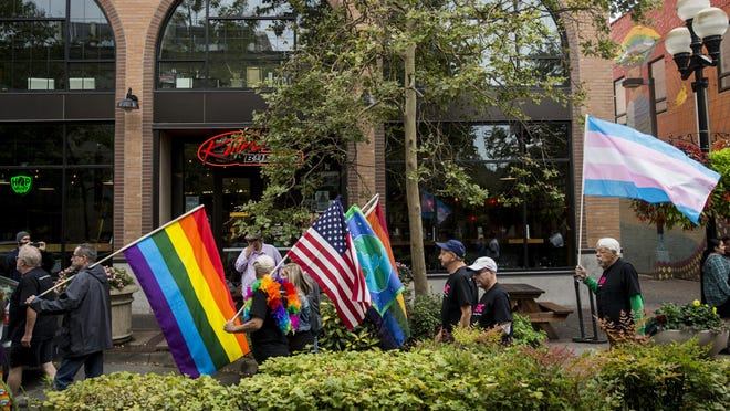 Marchers raise pride flags, the American flag and a flag with Earth pictured on it during the 2019 Eugene Springfield Pride event. [Dana Sparks/The Register-Guard file] - registerguard.com