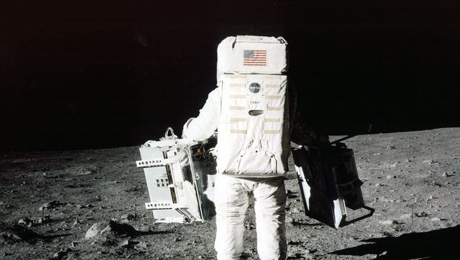 """FILE - In this July 20, 1969 file photo provided by NASA, Edwin """"Buzz"""" Aldrin carries scientific experiments to a deployment site south of the lunar module Eagle during the Apollo 11 mission. One experiment involved the inner composition of the moon, and another tried to determine the exact distance from Earth. Aldrin, 84, is asking everyone to remember where they were when he and Neil Armstrong became the first humans to walk on the moon and to share their memories online. (AP Photo/NASA, Neil Armstrong, File)"""