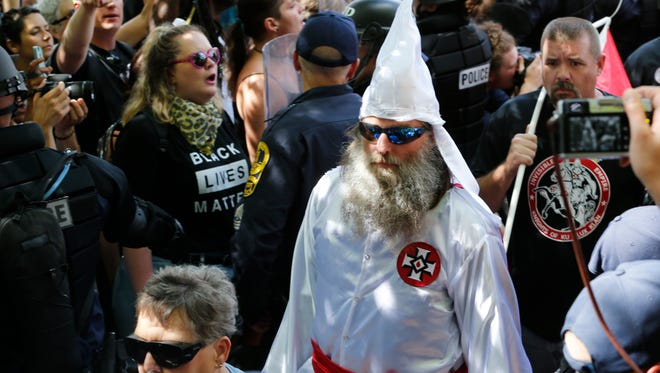 This July 8, 2017, photo shows members of the KKK escorted by police past a large group of protesters during a KKK rally in Charlottesville, Virginia. Some white Southerners are again advocating for what the Confederacy tried and failed to do in the 1860s: secession from the Union.