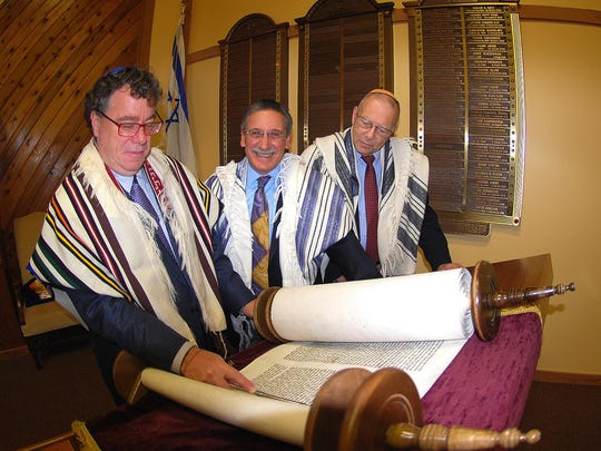 """Sam Kimelman, Bob Cohen and Irwin Kantrowitz, all """"Guardians of the Torah,"""" hold the Torah at the table on which it is read at Congregation Shomrei Torah. Kimelman will be honored on Jan. 28."""