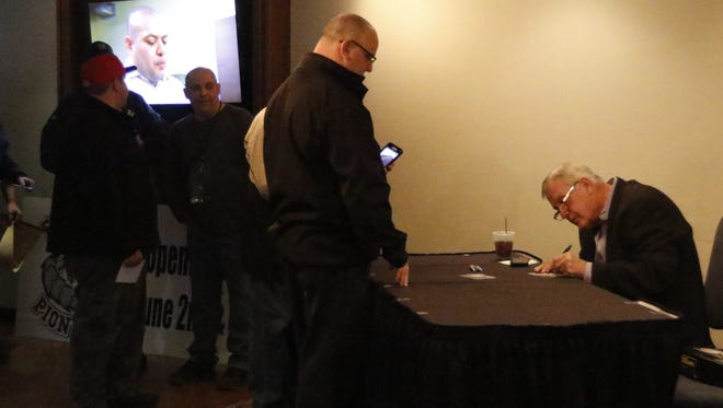 Former major league pitcher Tommy John signs autographs for fans Thursday as part of the Elmira Pioneers Hot Stove Dinner at the Holiday Inn-Riverview in Elmira.