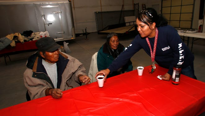 Volunteer Beronica Barber serves coffee to Cecil Billie and Marlene Cloud Thursday during an event to feed the homeless at the Shiprock Events Center.