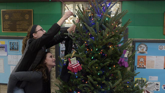 Maria Castrodale and Madeline Short, 13, light up the giving tree.