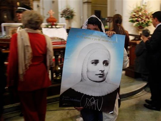 FILE - In this July 11, 2013 file photo, a woman holds a poster of Mother Laura Montoya or Madre Laura, inside the cathedral in Bogota, Colombia.