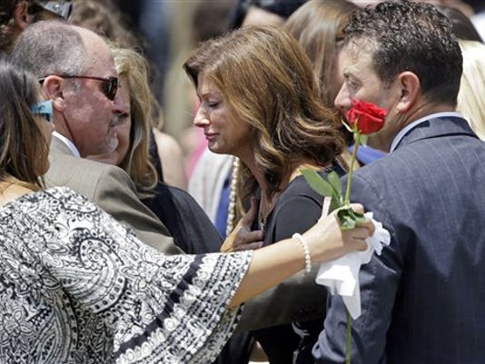 Dondie LeBlanc Breaux, mother of Mayci Breaux, center, and Kevin Breaux, right, father of Mayci, are comforted outside the Church of the Assumption, after her funeral in Franklin, La., Monday, July 27, 2015. She was one of two people killed in Thursday's movie theater shooting in Lafayette, La.