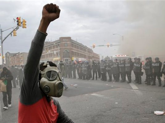 A demonstrator raises his fist as police stand in formation as a store burns, Monday, April 27, 2015, during unrest following the funeral of Freddie Gray in Baltimore.