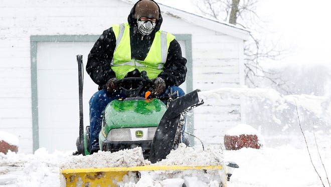 Justin Manke snow blows his driveway on Highway 26 between Rosendale and Waupun Wednesday morning after several inches of wet snow fell overnight. Doug Raflik/USA TODAY NETWORK-Wisconsin
