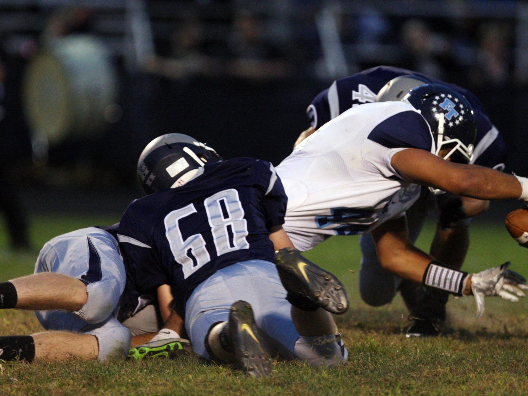 Nick Galenti, #44 Freehold Township, reaches for an extra yard as he is tackled by Eddie Roszkowski, #68 Howell, in a football game Friday, September 25, 2015, at Howell High School.