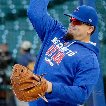 Kyle Schwarber throws  during workouts before the start