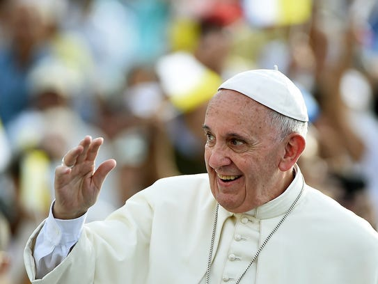 Pope Francis waves upon his arrival in Santiago de
