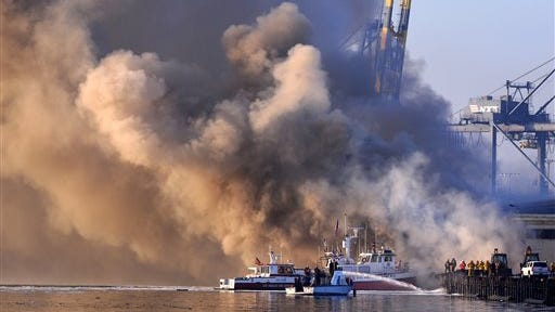 Los Angeles firefighters watch as smoke from a dock fire continues to rise as a fire boat sprays the underside of wooden pier timbers at the Port of Los Angeles in the Wilmington section of Los Angeles on Tuesday. The fire that forced evacuations from the wharf continues to smolder but officials say it's under control. Nearly 12 hours after starting, the blaze is sending up huge plumes of smoke that is drifting over Los Angeles Harbor early Tuesday. (AP Photo/The Daily Breeze, Brad Graverson)  MAGS OUT; NO SALES
