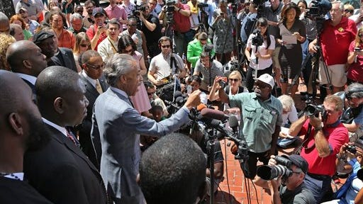 The Rev. Al Sharpton speaks on the steps of the Old Courthouse during a news conference Tuesday afternoon, Aug. 12, 2014, in St. Louis. Sharpton pressed police Tuesday to release the name of the officer who fatally shot an unarmed teenager in suburban St. Louis, but he also pleaded for calm after two nights of violent protests. (AP Photo/St. Louis Post-Dispatch, J. B. Forbes)