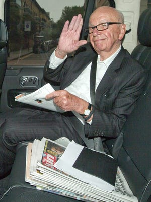 Media Mogul Rupert Murdoch waves to photographers as he is driven away from News UK headquarters in London June 26.