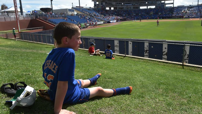 """Connor Buckley, 8, of Pearl River, New York, watches the final innings of the New York Mets split squad game against the Washington Nationals from the berm of First Data Field on Monday, March 27, 2017, in Port St. Lucie. """"Spring training, we're Mets obsessed,"""" said Laura Buckley, Connor's mother. The county is getting its $20 million from the state for renovations to First Data Field. Renovations to the stadium would include a players' academy, a cafeteria, executive offices, workout and training rooms, a 50-room dormitory for minor-league players and instructional rooms."""