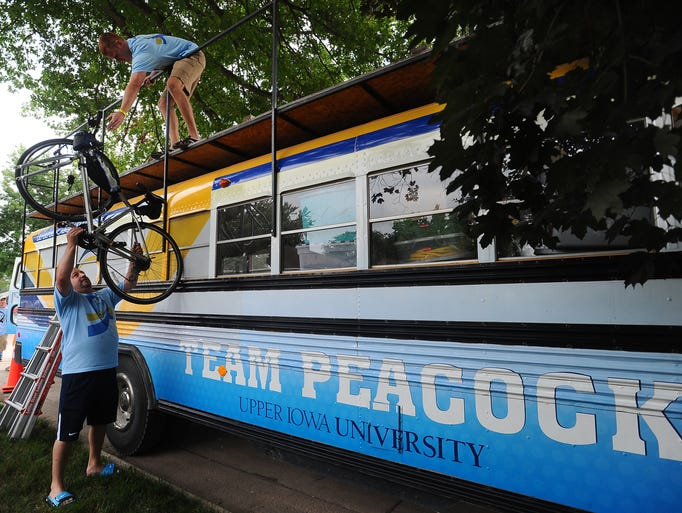 Storm Schmidt (top) and Tim Wolff with Upper Iowa University unload bikes during RAGBRAI in Rock Valley on Saturday, July 19, 2014.