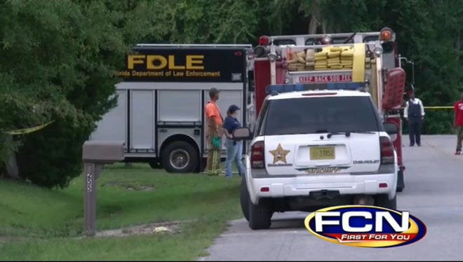 Florida Department of Law Enforcement and Union County Sheriff's Office officials gather Aug. 24, 2013, in Lake Butler, Fla., after a former trucking company employee shoots 4 co-workers and then himself.
