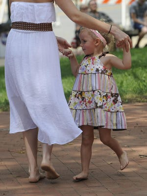 Cordelia Graves dances with her mother, Tina Wears, during Agent 99's performance Wednesday at the bandstand in downtown Lancaster.