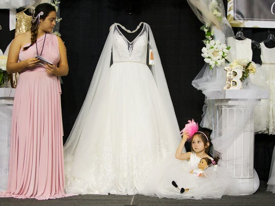 Flower girl Tyler Moore, 6, gets some much needed rest Sunday during the Southwest Florida Bridal Show at the Suncoast Credit Union Arena at Florida Southwestern State College in south Fort Myers. Tyler and Ezri Damschroder, 16, right, modeled fashions for Carina's Bridal of Cape Coral. Vendors from throughout Florida showcased dresses, tuxedos, photography, cakes and other services.