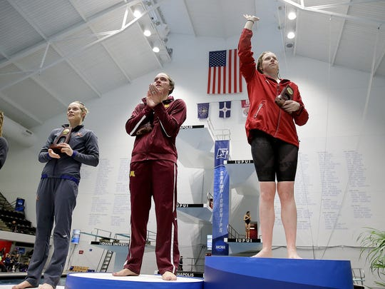 Indiana University's Lilly King waves to the fans and holds her  trophy after winning the Women's 100 Yard breaststroke at the NCAA Women's Swimming & Diving championships Friday at the Natatorium at IUPUI in Indianapolis. Minnesota's Lindsey Horejsi,middle, took 2nd place and UVA's Laura Simon,left, placed third.