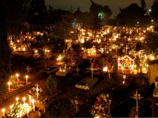 Candles illuminate grave sites at the San Gregorio