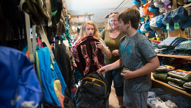 Holder of the purse strings, Janine Lang shepherds children Olivia and Elias through the backpacks at Take A Hike Outfitters in Black Mountain recently.